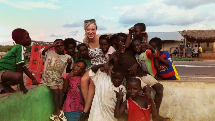 Volunteer together with a group of children from Ghana standing in front of Ghanaian houses.